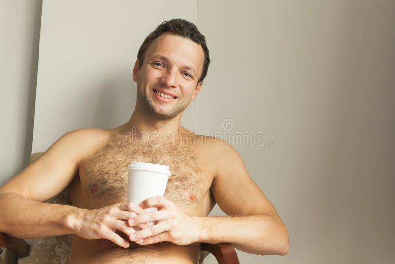 Πορτρέτο του νέου χαμογελώντας ευρωπαϊκού ατόμου με το φλυτζάνι στοκ εικόνα