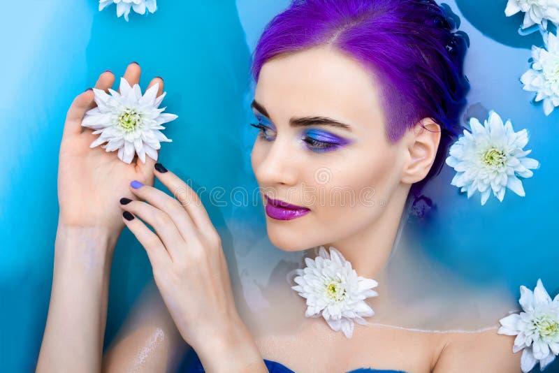 Πορτρέτο του νέου χαριτωμένου θηλυκού προτύπου πολυτέλειας μόδας στην μπανιέρα με τα λουλούδια στοκ εικόνες