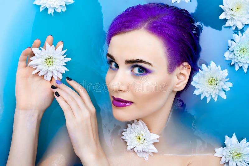 Πορτρέτο του νέου χαριτωμένου θηλυκού προτύπου πολυτέλειας μόδας στην μπανιέρα με τα λουλούδια στοκ εικόνα