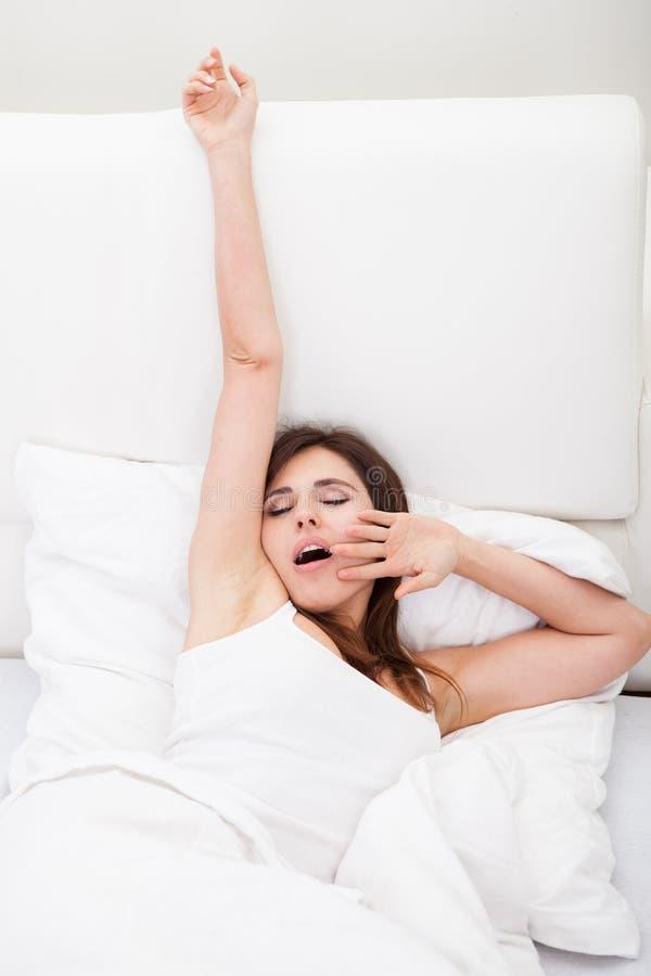 Νέα γυναίκα που χασμουριέται στο κρεβάτι στοκ φωτογραφία με δικαίωμα ελεύθερης χρήσης