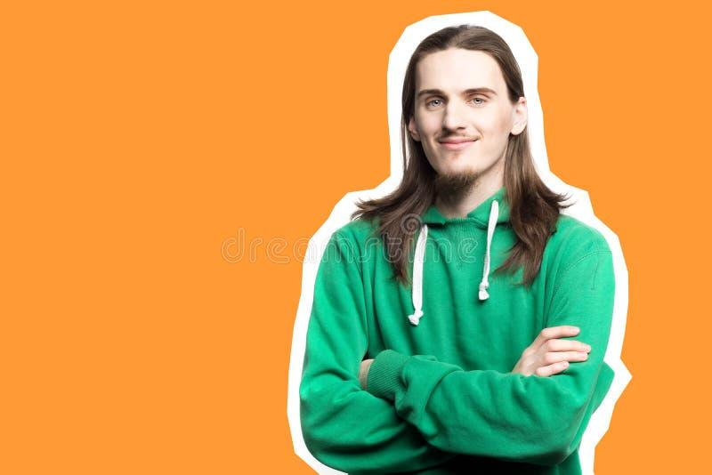 Πορτρέτο του νέου όμορφου ατόμου στο πράσινο hoodie που κοιτάζει στο πορτοκαλί υπόβαθρο καμερών agains, κολάζ τέχνης στοκ εικόνα με δικαίωμα ελεύθερης χρήσης