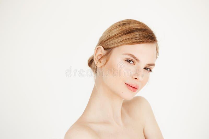 Πορτρέτο του νέου όμορφου κοριτσιού με το υγιές καθαρό χαμόγελο δερμάτων που εξετάζει τη κάμερα πέρα από το άσπρο υπόβαθρο facial στοκ φωτογραφίες