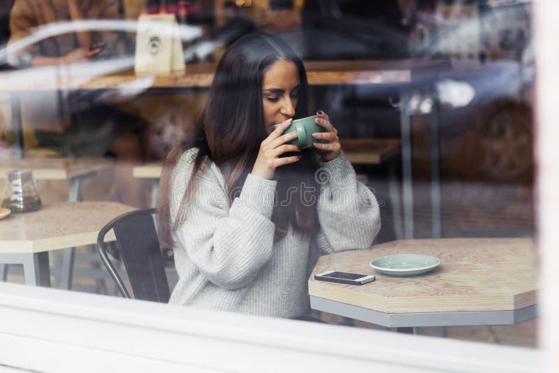 πορτρέτο του νέου όμορφου χαριτωμένου κοριτσιού brunette στον γκρίζο καφέ κατανάλωσης πουλόβερ στοκ εικόνα με δικαίωμα ελεύθερης χρήσης