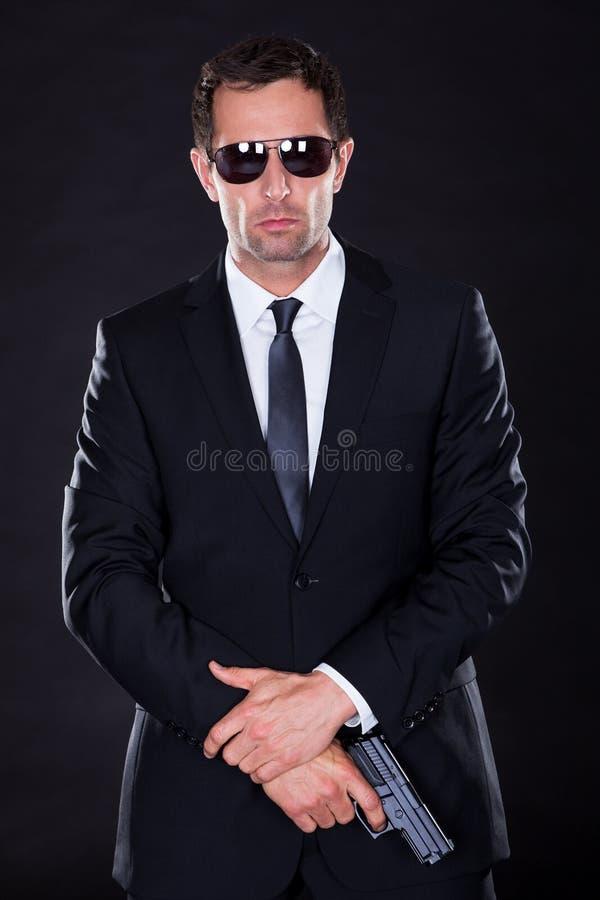 Πορτρέτο του νεαρού άνδρα με το πυροβόλο όπλο στοκ εικόνα