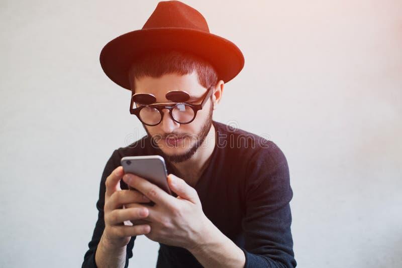 Πορτρέτο του νεαρού άνδρα με το smartphone στα χέρια, που φορούν το μαύρο καπέλο και τα γυαλιά ηλίου στοκ φωτογραφίες με δικαίωμα ελεύθερης χρήσης