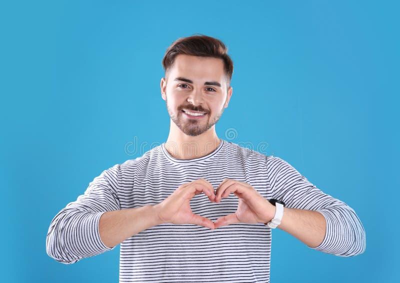 Πορτρέτο του νεαρού άνδρα που κατασκευάζει την καρδιά με τα χέρια του στοκ φωτογραφία με δικαίωμα ελεύθερης χρήσης