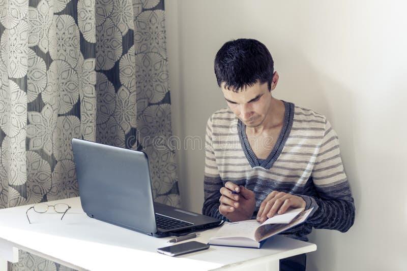 Πορτρέτο του νεαρού άνδρα στην περιστασιακή ένδυση στην εργασία που λειτουργεί στο lap-top, που κάνει τις σημειώσεις στο σημειωμα στοκ φωτογραφίες με δικαίωμα ελεύθερης χρήσης