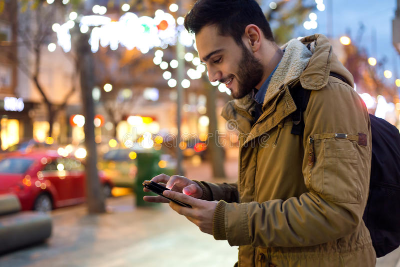 Πορτρέτο του νεαρού άνδρα που χρησιμοποιεί το κινητό τηλέφωνό του στην οδό στο Νι στοκ εικόνες με δικαίωμα ελεύθερης χρήσης