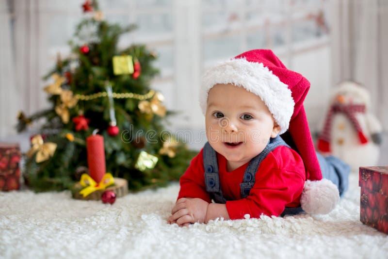 Πορτρέτο του νεογέννητου μωρού στα ενδύματα Santa και το καπέλο Χριστουγέννων στοκ εικόνες με δικαίωμα ελεύθερης χρήσης