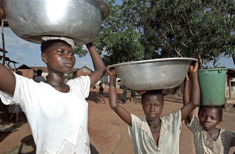 Πορτρέτο του νερού που φέρνει τα κορίτσια κατοίκων της Γκάνας, Γκάνα στοκ εικόνα