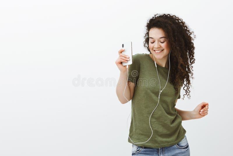 Πορτρέτο του ξένοιαστου όμορφου μοντέρνου κοριτσιού με τη σγουρή τρίχα, που χορεύει με τις ιδιαίτερες προσοχές και το ευρύ χαμόγε στοκ εικόνα