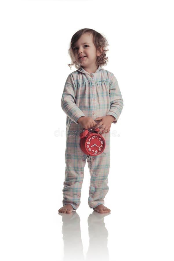Πορτρέτο του ξυπνητηριού εκμετάλλευσης μικρών κοριτσιών που απομονώνεται πέρα από το λευκό στοκ φωτογραφία με δικαίωμα ελεύθερης χρήσης