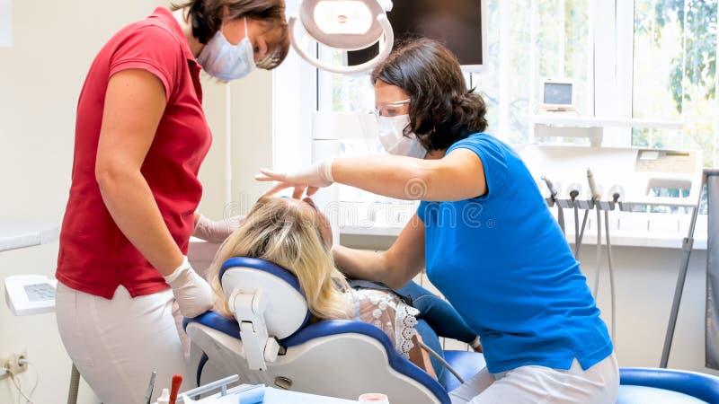 Πορτρέτο του οδοντιάτρου και του βοηθητικού treting ασθενή στοκ εικόνες με δικαίωμα ελεύθερης χρήσης
