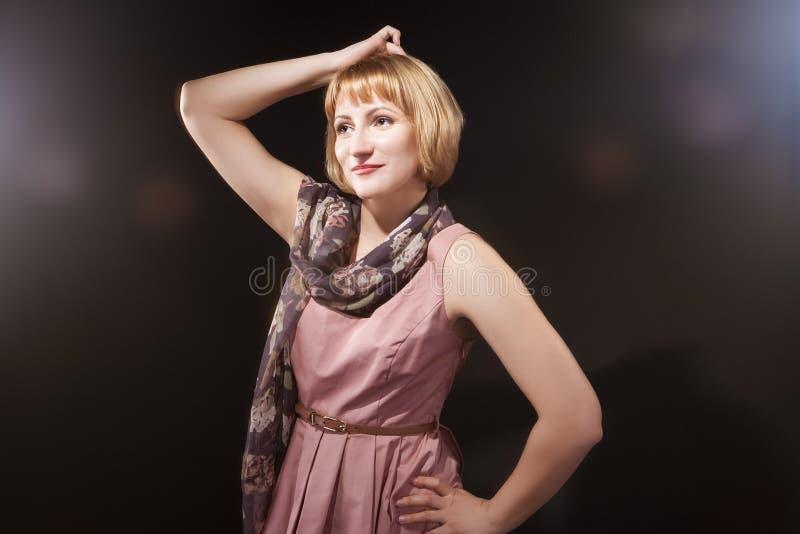 Πορτρέτο του οπτιμιστούς αισιόδοξου καυκάσιου ξανθού θηλυκού στο ρόδινο φόρεμα στοκ εικόνα