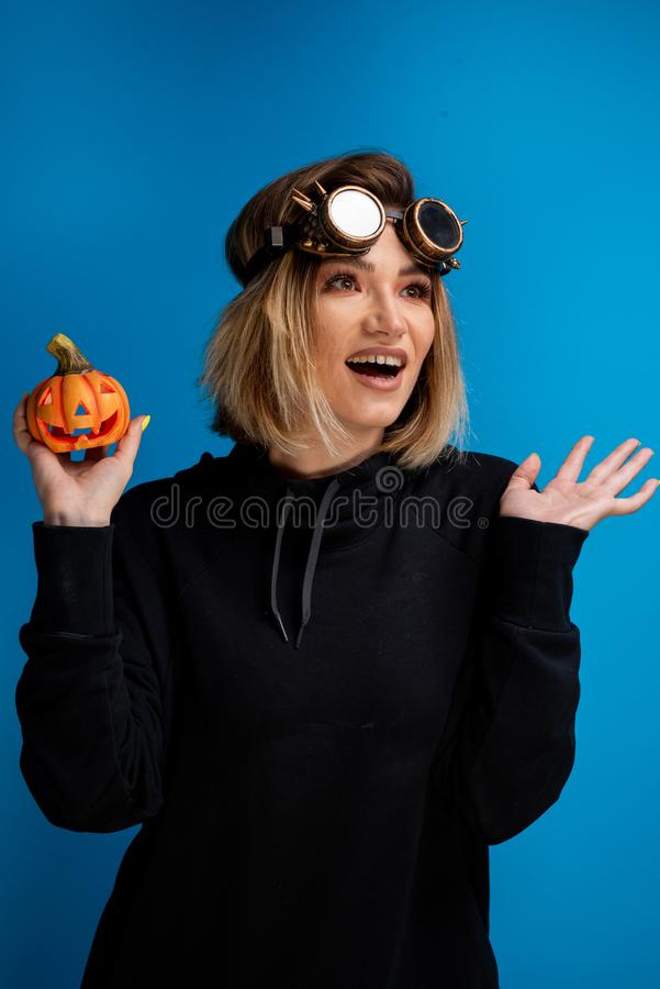 Πορτρέτο του πανκ κοριτσιού ατμού που φορά ένα μαύρο hoodie που κρατά ψηλά μια χαρασμένη κολοκύθα αποκριών στοκ εικόνες