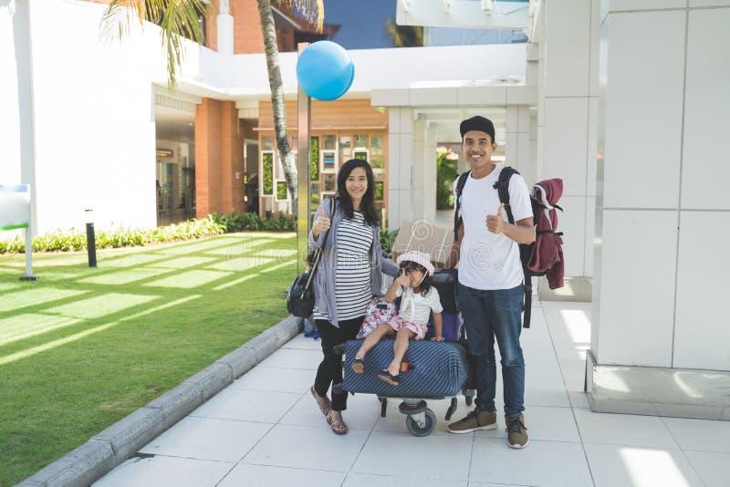 Πορτρέτο του πατέρα, της μητέρας και της κόρης τους που χαμογελούν με τον αντίχειρα επάνω ενώ εξετάστε τη κάμερα στοκ εικόνες