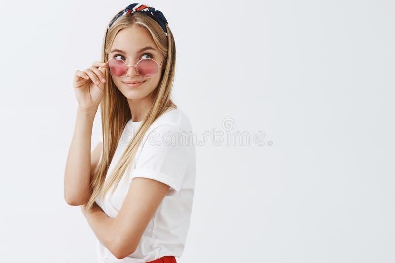 Πορτρέτο του περίεργου και ραδιουργημένου ελκυστικού ξανθού θηλυκού στα καθιερώνοντα τη μόδα γυαλιά ηλίου και τη θηλυκή εξάρτηση  στοκ φωτογραφία με δικαίωμα ελεύθερης χρήσης
