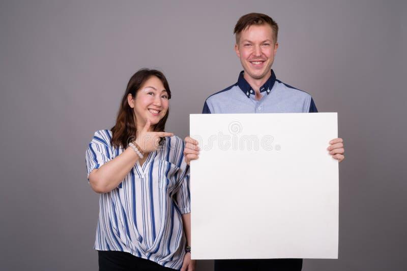 Πορτρέτο του πολυ εθνικού διαφορετικού ζεύγους στο στούντιο που παρουσιάζει διάστημα αντιγράφων στοκ φωτογραφίες με δικαίωμα ελεύθερης χρήσης