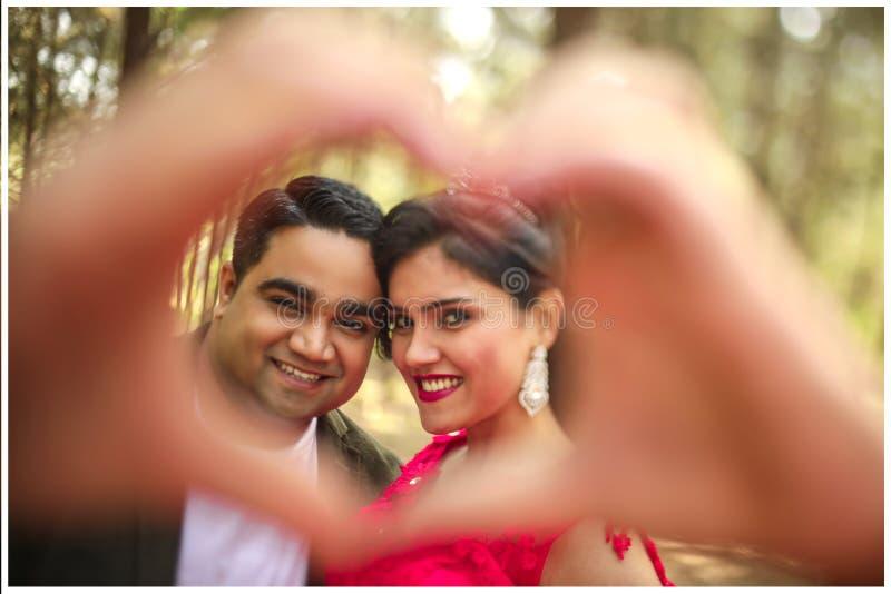 Πορτρέτο του ρομαντικού ζεύγους ερωτευμένο gesturing μια καρδιά με τα δάχτυλα στοκ εικόνες