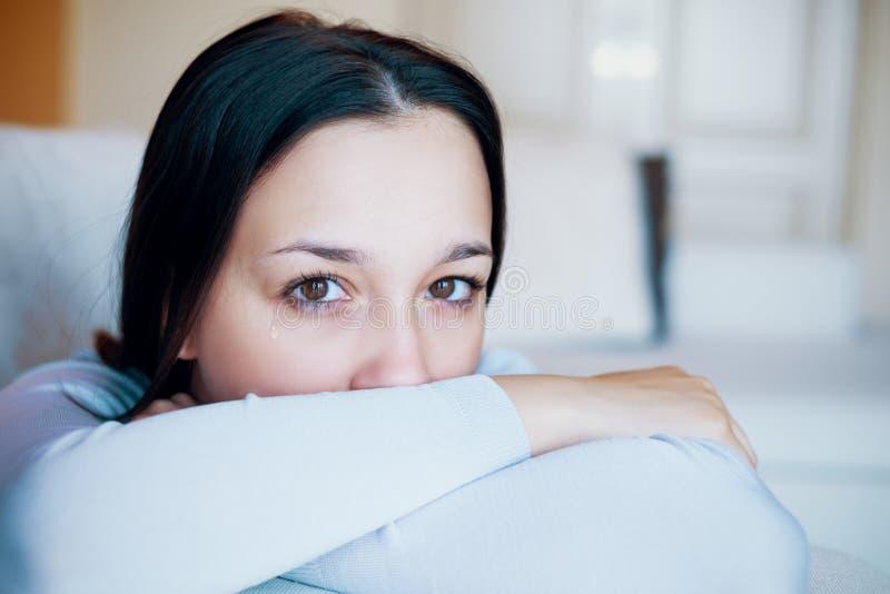 Πορτρέτο του σκεπτικού νέου κοριτσιού στον καναπέ στοκ φωτογραφία με δικαίωμα ελεύθερης χρήσης