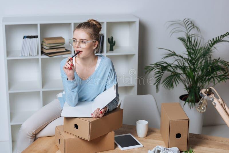 πορτρέτο του σκεπτικού σε απευθείας σύνδεση ιδιοκτήτη καταστημάτων με τη μάνδρα και του σημειωματάριου που εξετάζει μακριά τον πί στοκ εικόνες με δικαίωμα ελεύθερης χρήσης