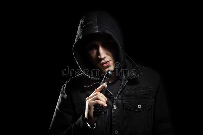 Πορτρέτο του σοβαρού ατόμου με το πυροβόλο όπλο στο Μαύρο κουκουλών στοκ φωτογραφία με δικαίωμα ελεύθερης χρήσης