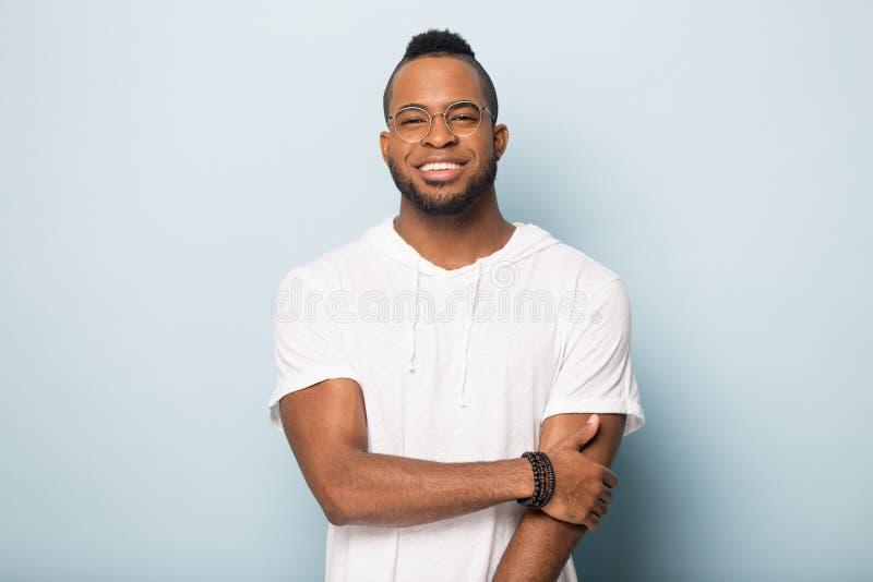 Πορτρέτο του σοβαρού μαύρου που απομονώνεται στο μπλε υπόβαθρο στούντιο στοκ φωτογραφία