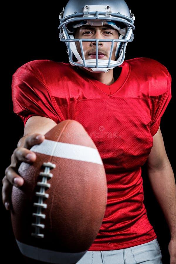 Πορτρέτο του σοβαρού φορέα αμερικανικού ποδοσφαίρου που παρουσιάζει σφαίρα στοκ εικόνα