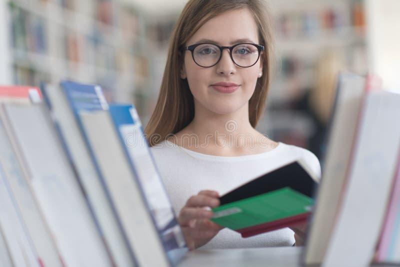 Πορτρέτο του σπουδαστή famale που επιλέγει το βιβλίο που διαβάζει στη βιβλιοθήκη στοκ φωτογραφία με δικαίωμα ελεύθερης χρήσης