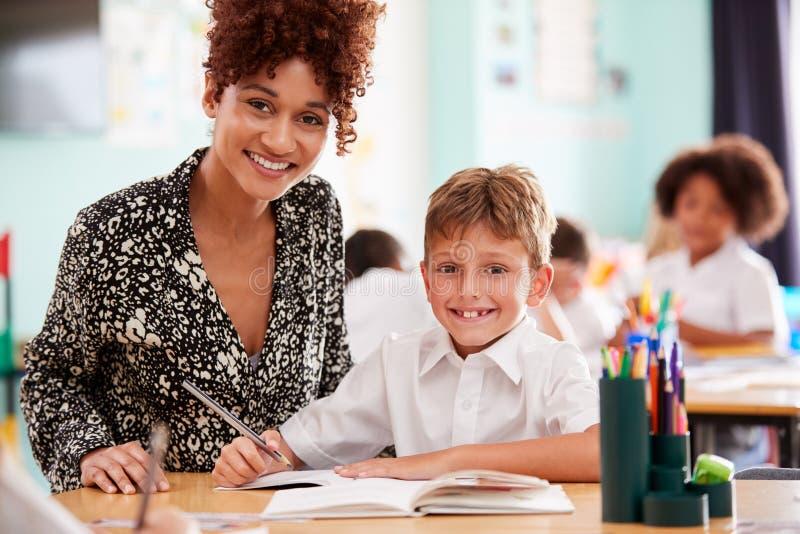 Πορτρέτο του στοιχειώδους δασκάλου σχολείου γυναικών που δίνει τον αρσενικό μαθητή που φορά ομοιόμορφη μια έως μια υποστήριξη στοκ φωτογραφία με δικαίωμα ελεύθερης χρήσης