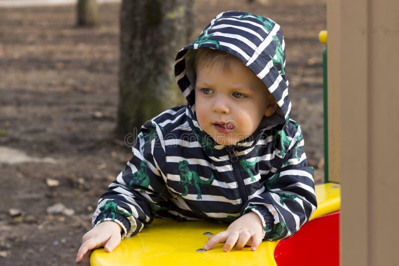 Πορτρέτο του στοχαστικού παιχνιδιού μικρών παιδιών έξω στην παιδική χαρά, λατρευτό μικρό παιδί σε μια κουκούλα που παίζει υπαίθρι στοκ φωτογραφίες με δικαίωμα ελεύθερης χρήσης