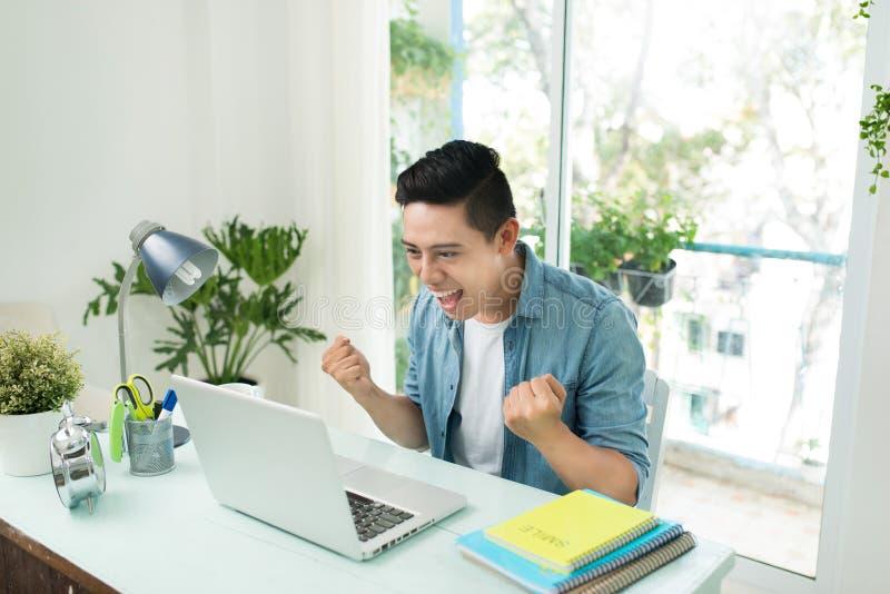 Πορτρέτο του συγκινημένου ασιατικού νεαρού άνδρα που εργάζεται στο φορητό προσωπικό υπολογιστή α στοκ εικόνες