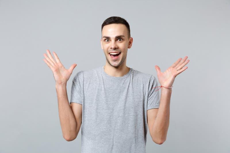 Πορτρέτο του συγκινημένου αστείου νεαρού άνδρα στα περιστασιακά ενδύματα που κρατούν χέρια τα στοματικών ανοικτά, διάδοσης απομον στοκ φωτογραφία
