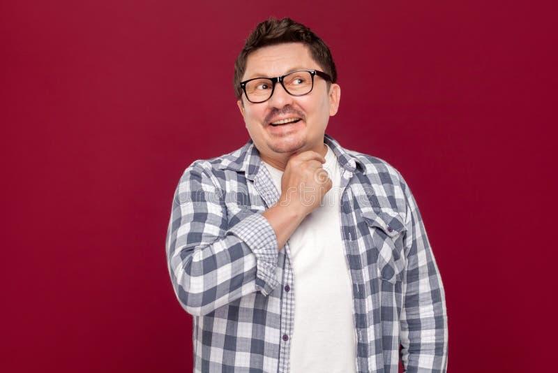 Πορτρέτο του συλλογιμένος όμορφου μέσου ηλικίας επιχειρησιακού ατόμου smiley στο περιστασιακό ελεγμένο πουκάμισο και eyeglasses τ στοκ φωτογραφία με δικαίωμα ελεύθερης χρήσης