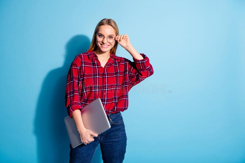 Πορτρέτο του συμπαθητικού γοητευτικού ελκυστικού χαριτωμένου εύθυμου κοριτσιού εφήβων που φορά το ελεγχμένο φέρνοντας lap-top που στοκ εικόνα