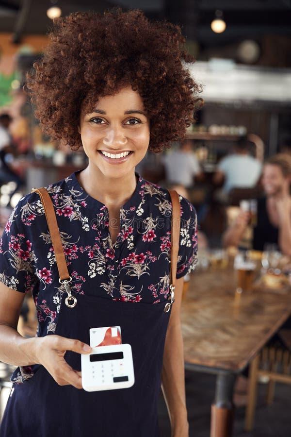 Πορτρέτο του τερματικού πληρωμής με πιστωτική κάρτα εκμετάλλευσης σερβιτορών στο πολυάσχολο εστιατόριο φραγμών στοκ εικόνες με δικαίωμα ελεύθερης χρήσης