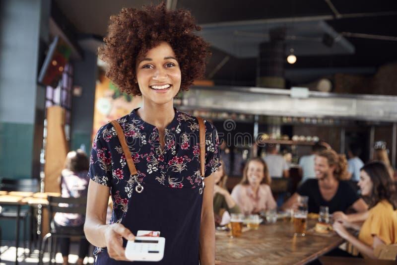 Πορτρέτο του τερματικού πληρωμής με πιστωτική κάρτα εκμετάλλευσης σερβιτορών στο πολυάσχολο εστιατόριο φραγμών στοκ φωτογραφίες