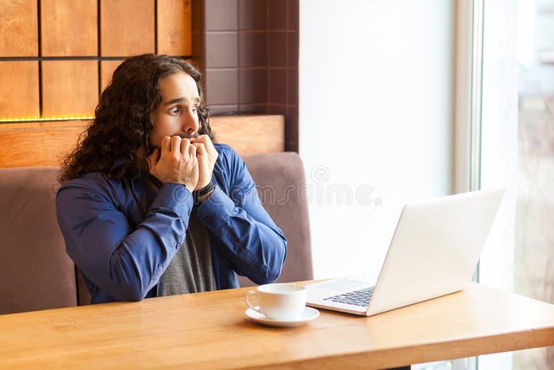 Πορτρέτο του φοβησμένου όμορφου νέου ενήλικου ατόμου freelancer στην περιστασιακή συνεδρίαση ύφους στον κινηματογράφο φρικών καφέ στοκ εικόνες