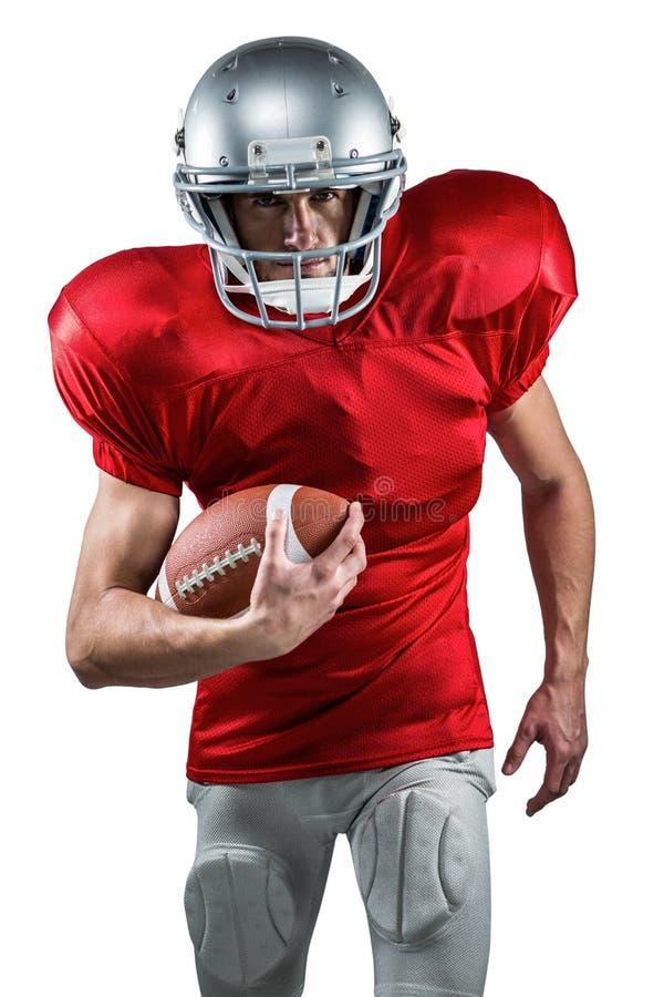 Πορτρέτο του φορέα αμερικανικού ποδοσφαίρου στο κόκκινο Τζέρσεϋ που τρέχει με τη σφαίρα στοκ εικόνα