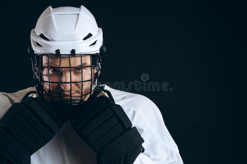 Πορτρέτο του φορέα πάγος-χόκεϋ με το ραβδί χόκεϋ και τα προστατευτικά γάντια στοκ φωτογραφία