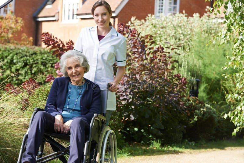 Πορτρέτο του φροντιστή που ωθεί την ανώτερη γυναίκα στην αναπηρική καρέκλα στοκ φωτογραφίες