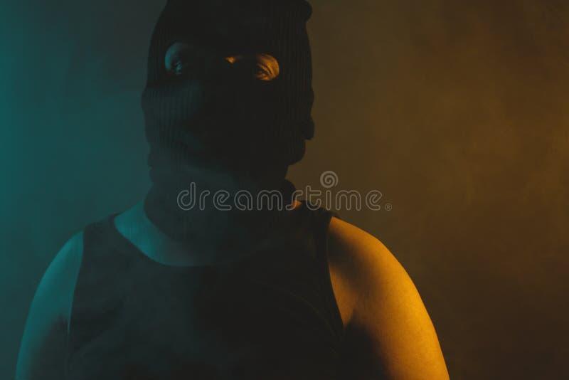 Πορτρέτο του χαλαρωμένου ατόμου μαύρο balaclava, που φωτίζεται από το αφηρημένο φως στα πράσινα και κίτρινα χρώματα στοκ εικόνες
