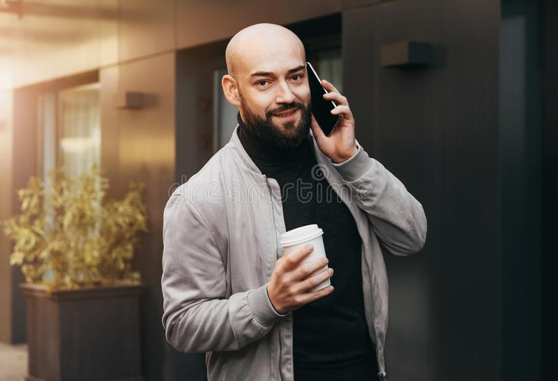 Πορτρέτο του χαμογελώντας ατόμου που μιλά στο τηλέφωνο κυττάρων και τον καφέ κατανάλωσης στην οδό πόλεων, γενειοφόρος τύπος hipst στοκ εικόνες