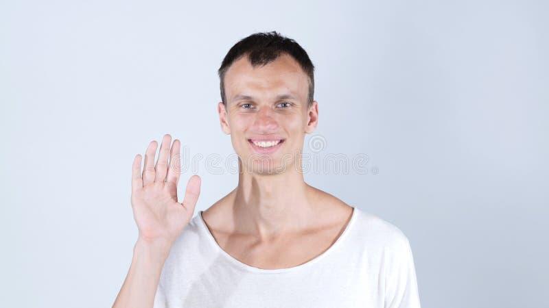 πορτρέτο του χαμογελώντας ατόμου που στέκεται και που παρουσιάζει σημάδι χεριών γεια και αντίο στοκ εικόνα