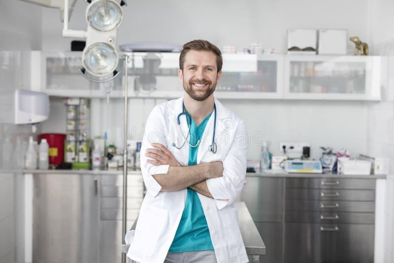 Πορτρέτο του χαμογελώντας γιατρού που στέκεται με τα όπλα που διασχίζονται στην κτηνιατρική κλινική στοκ φωτογραφίες