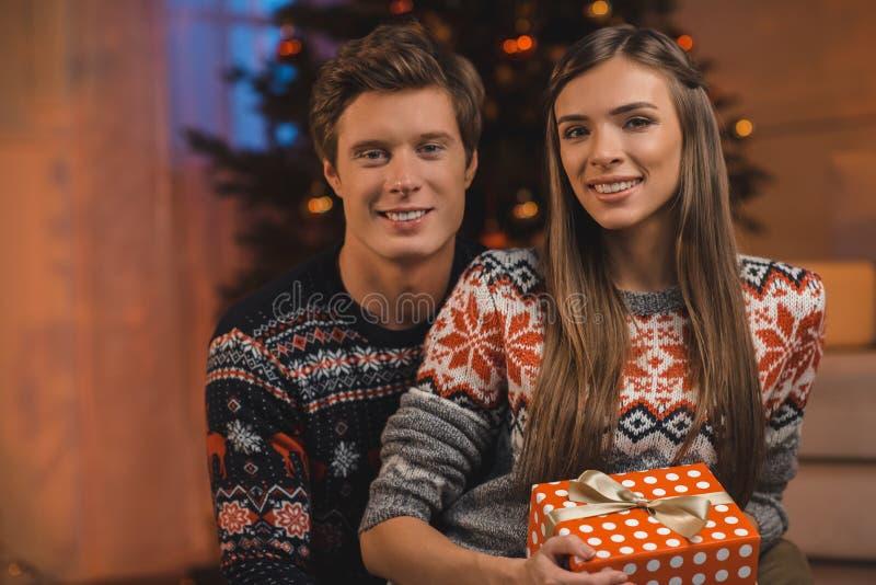 πορτρέτο του χαμογελώντας ζεύγους στα πουλόβερ και του δώρου Χριστουγέννων στο κοίταγμα χεριών στοκ φωτογραφίες με δικαίωμα ελεύθερης χρήσης
