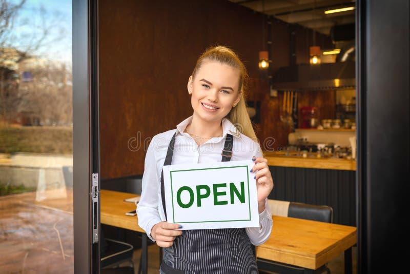 Πορτρέτο του χαμογελώντας ιδιοκτήτη που στέκεται στην πόρτα εστιατορίων που κρατά το ανοικτό σημάδι, μικρή οικογενειακή επιχείρησ στοκ φωτογραφία