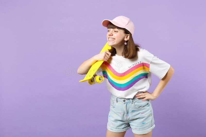 Πορτρέτο του χαμογελώντας κοριτσιού εφήβων στα ζωηρά ενδύματα που κρατά κίτρινο skateboard, που φαίνεται κατά μέρος απομονωμένο σ στοκ φωτογραφία με δικαίωμα ελεύθερης χρήσης