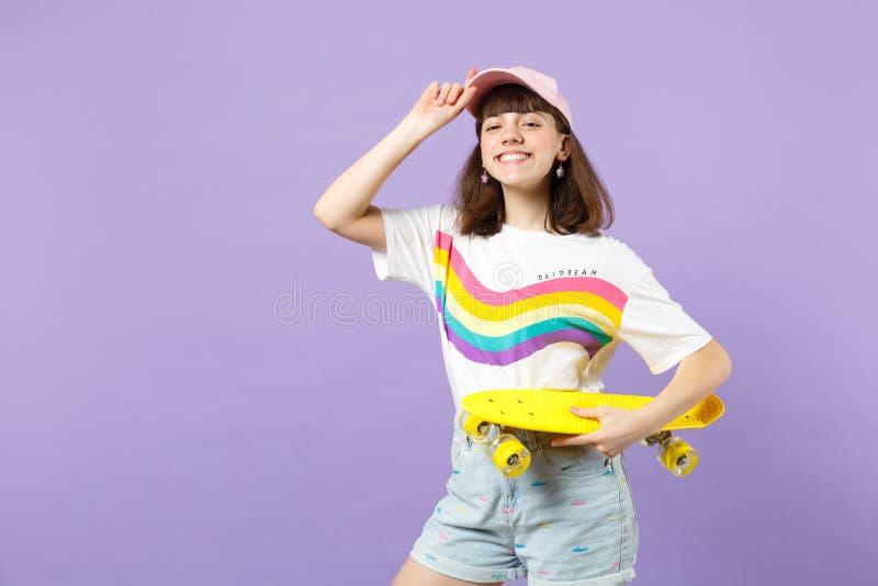 Πορτρέτο του χαμογελώντας κοριτσιού εφήβων στα ζωηρά ενδύματα που φαίνεται κάμερα, που κρατά κίτρινο skateboard απομονωμένο στην  στοκ εικόνες