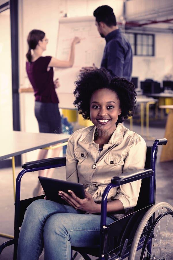 Πορτρέτο του χαμογελώντας με ειδικές ανάγκες ανώτατου στελέχους επιχείρησης στην αναπηρική καρέκλα που χρησιμοποιεί την ψηφιακή τ στοκ φωτογραφίες με δικαίωμα ελεύθερης χρήσης